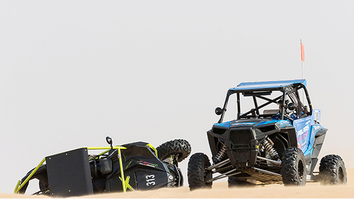 one-of-the-polaris-uae-team-passing-a-rolled-canam-of-chris-jackson